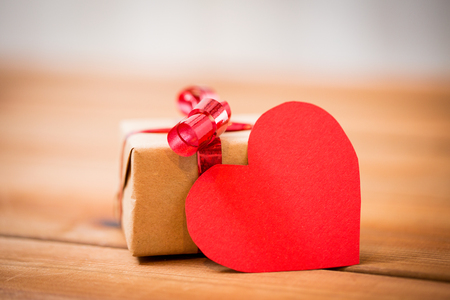 attentions: love, date, romance, valentines day and holidays concept - close up of gift box and blank red heart-shaped note on wood Stock Photo