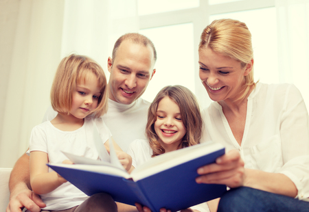 pre adult: family, child and home concept - smiling family and two little girls with book at home Stock Photo