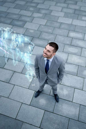 top of the world: business, development and people concept - young smiling businessman with world map hologram outdoors from top