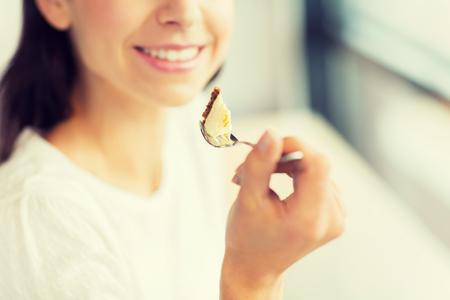 comida, postre, las personas y el concepto de estilo de vida - primer plano de mujer joven sonriente sosteniendo un tenedor y comer pastel en el café o en el hogar