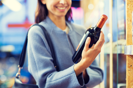 choosing: sale, shopping, consumerism and people concept - happy young woman choosing and buying wine in market or liquor store