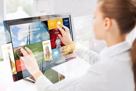 screen search: business, people, technology and mass media concept - woman with web pages on computer touchscreen in office Stock Photo