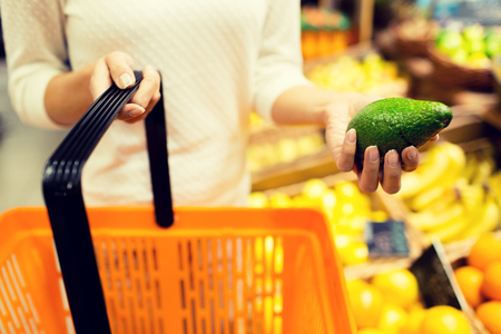 supermarkets: sale, shopping, consumerism and people concept - close up of young woman with food basket and avocado in market Stock Photo