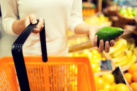 supermercado: venta, compras, consumismo y el concepto de la gente - cerca de la mujer joven con canasta de alimentos y aguacate en el mercado Foto de archivo