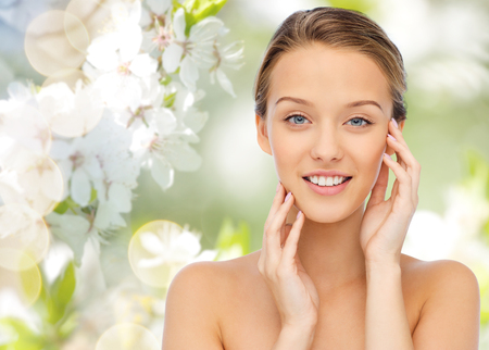 natural face: beauty, people and health concept - smiling young woman with bare shoulders touching her face over green natural background with cherry blossom