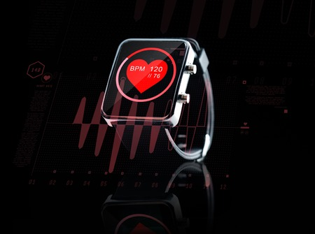 health technology: modern technology, object, health care and media concept - close up of black smart watch showing red heart beat icon on screen and cardiogram Stock Photo