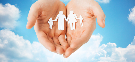 values: people, values and happiness concept - close up of man cupped hands showing paper family cutout over blue sky and clouds background Stock Photo