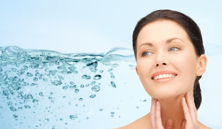 beauty, people, moisturizing and health concept - smiling young woman with shoulders touching her face over water splash on blue background