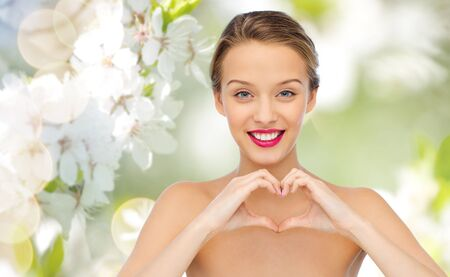 eco green: beauty, people, love, valentines day and make up concept - smiling young woman with pink lipstick on lips showing heart shape hand sign over green natural background with cherry blossom