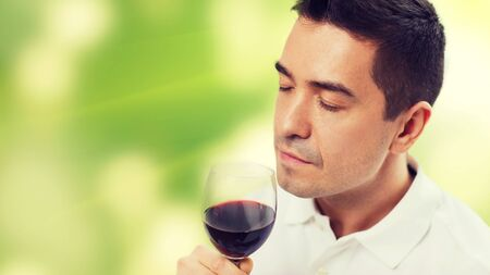 latin man: profession, drinks, leisure and people concept - happy man drinking and smelling red wine from glass over green background