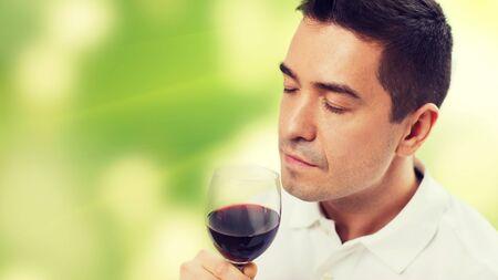 uomo rosso: professione, bevande, il tempo libero e la gente concept - felice l'uomo a bere e profumato vino rosso di vetro su sfondo verde Archivio Fotografico