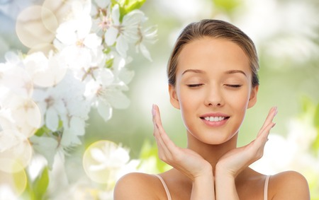 beauty, people, skincare and health concept - smiling young woman face and hands over green natural background with cherry blossom