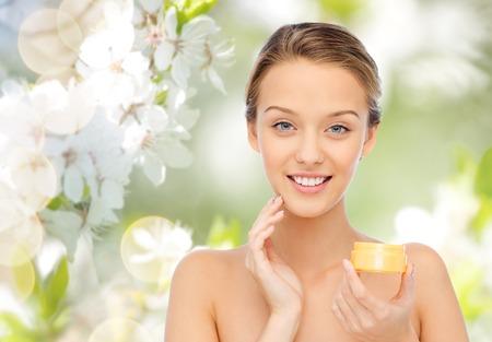 belleza, gente, cosméticos, cuidado de la piel y cosméticos concepto - mujer joven feliz que aplica la crema a su cara sobre el fondo verde natural con flor de cerezo