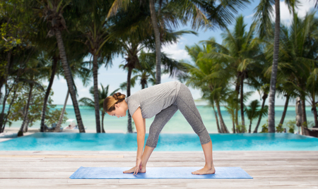 beach mat: fitness, sport, people and healthy lifestyle concept - woman making yoga intense stretch pose on mat over hotel resort pool on tropical beach background