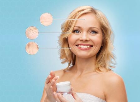 schoonheid, mensen, huidverzorging, anti-aging en cosmetica concept - gelukkig vrouw van middelbare leeftijd met zalfpotje over blauwe achtergrond