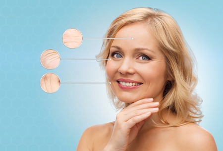 antiaging: beauty, people, anti-aging and skincare concept - smiling middle aged woman with bare shoulders touching face over blue background Stock Photo