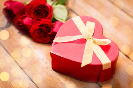 uprzejmości: love, date, romance, valentines day and holidays concept - close up of heart shaped gift box and red roses on wooden table