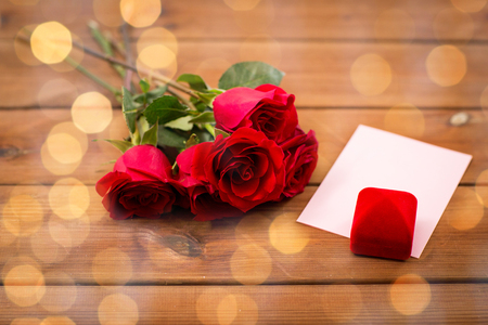 uprzejmości: love, romance, valentines day and holidays concept - close up of gift box, red roses and greeting card on wood