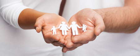 love and relationships concept - closeup of couple cupped hands showing paper man family Stock Photo