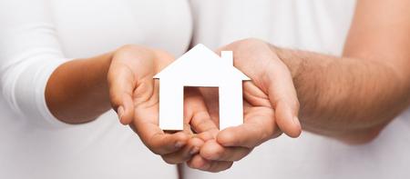 concetto di proprietà immobiliare e familiare - closeup di coppia mani azienda carta casa
