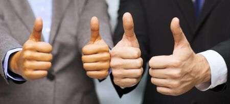 co workers: business and office concept - businessman and businesswoman showing thumbs up in office Stock Photo
