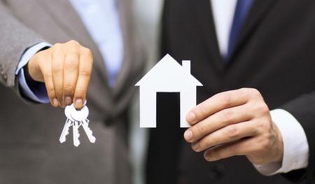 Zakelijke, eco, onroerend goed en kantoor concept - zakenman en zakenvrouw bedrijf wit papier huis en sleutels in kantoor