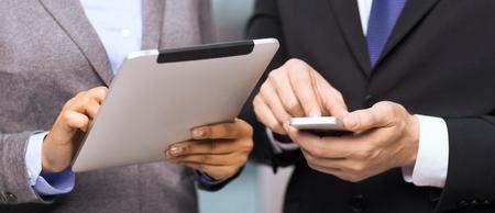 Business, technologie, internet et concept de bureau - homme d'affaires et femme d'affaires avec smartphone et tablette PC au bureau Banque d'images