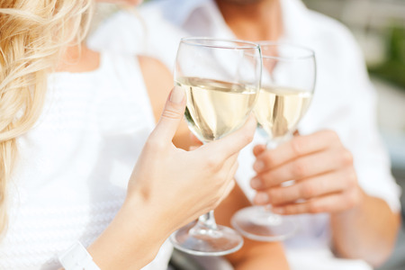 summer holidays and dating concept - couple drinking wine in cafe in the city