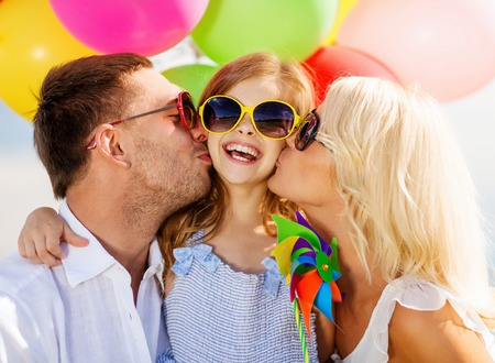 children party: summer holidays, celebration, children and people concept - family with colorful balloons