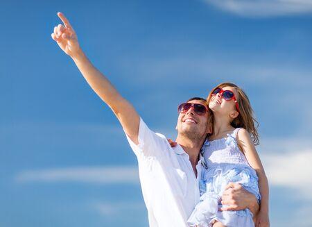 Zomervakantie, kinderen en mensen concept - gelukkige vader en kind in zonnebril over blauwe lucht