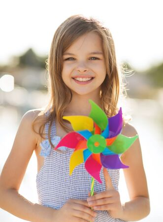 pre teen girls: summer holidays, celebration, family, children and people concept - happy girl with colorful pinwheel toy