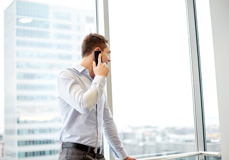 out of office: business, technology and people concept - happy businessman calling on smartphone and looking out office window Stock Photo