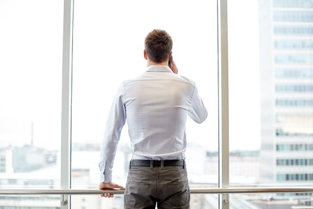 out of office: business, technology and people concept - businessman calling on smartphone and looking out office window