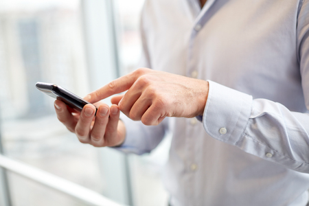 working man: business, technology and people concept - close up of man hands with smartphone texting message or dialing number at office Stock Photo
