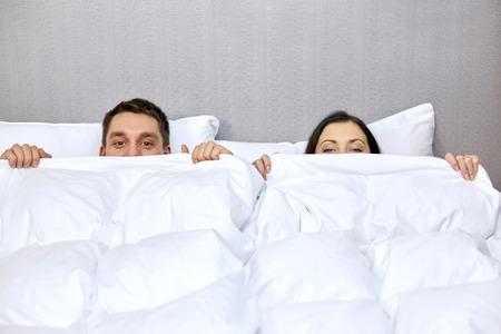Menschen, Schlafenszeit, Komfort und Beziehungen Konzept - Konzept - glückliche Paar im Bett unter Decke versteckt Standard-Bild