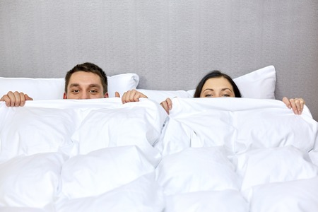 people, bedtime, comfort and relations concept - concept - happy couple hiding under blanket in bed