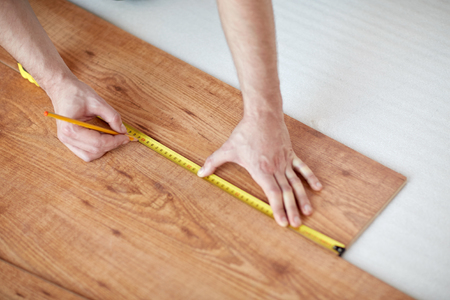 yardstick: repair, building, floor and people concept - close up of male hands measuring wooden flooring with ruler and making mark by pencil