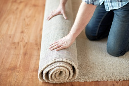repair, building and home concept - close up of male hands rolling carpet 写真素材