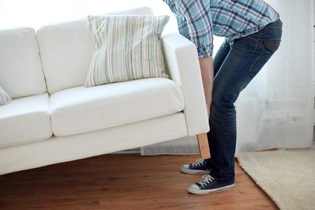 nuevo hogar, bienes raíces, el movimiento y concepto de mobiliario - cerca de sexo masculino que levanta encima de un sofá o un sofá