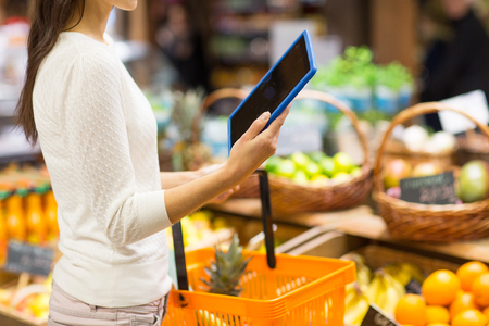 biology: sale, shopping, consumerism and people concept - close up of young woman with food basket and tablet pc computer in market