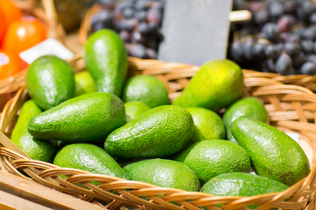 fruits in a basket: sale, shopping, vitamin c and eco food concept - ripe avocado in basket at food market