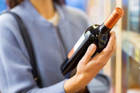 Verkauf, Einkaufen, Konsum und Menschen Konzept - glückliche junge Frau, die Auswahl und Wein in Markt oder Spirituosengeschäft kaufen