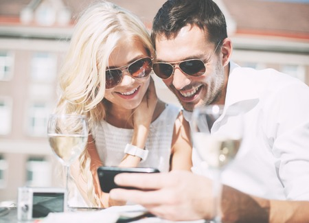 couple outdoor: summer holidays, dating and technology concept - couple looking at smartphone in cafe in the city Stock Photo