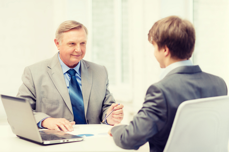 two men: business, technology and office concept - older man and young man having meeting in office