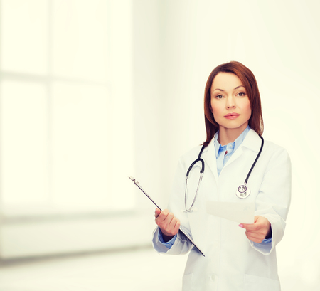health professional: healthcare and medicine concept - calm female doctor with clipboard and stethoscope