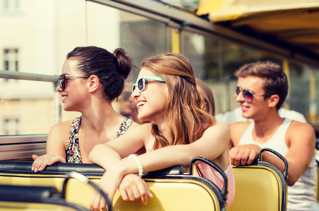 buses: friendship, travel, vacation, summer and people concept - group of smiling friends traveling by tour bus