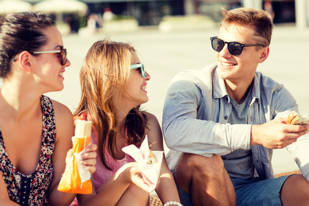 hot summer: friendship, leisure, summer and people concept - group of smiling friends in sunglasses sitting with food on city square