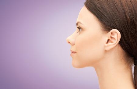 kunststoff: Gesundheit, Menschen, plastische Chirurgie und Beauty-Konzept - schöne junge Frau Gesicht auf violettem Hintergrund