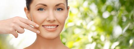 医療・人・美容コンセプト - 緑の自然な背景の上彼女の顔の皮膚に触れる美しい女性