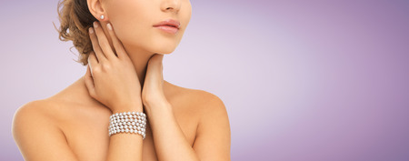 string of pearls: beauty, people and jewelry concept - close up of beautiful woman with pearl earrings and bracelet over violet background